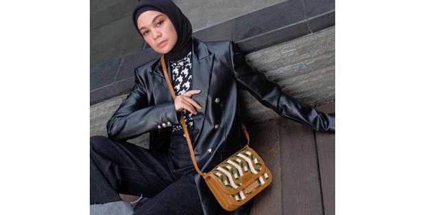 Tantri Namirah tampil berbeda dengan memadukan hijab dan jaket kulit. Tas kulit dengan motif retro geometris tampil outstanding